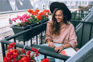 Woman smiling working with her laptop at a balcony
