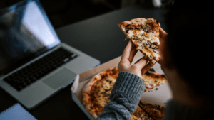 A person working in the laptop and eating pizza