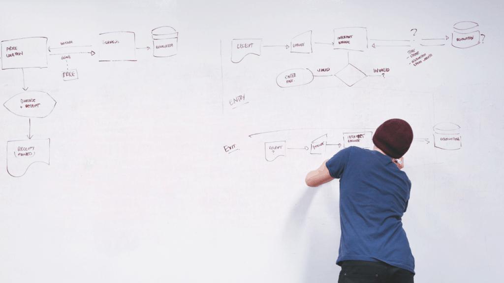 Man writing in a whiteboard.