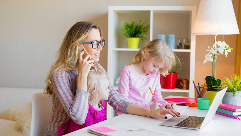 Woman working from home and taking care of her daughters