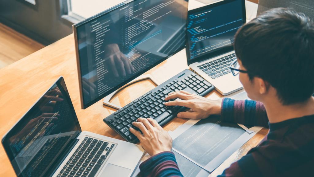 developer coding in multiple monitors