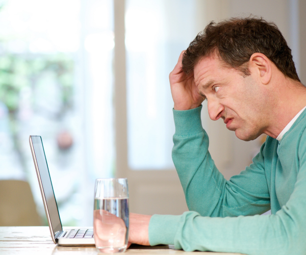 confused man looking at laptop screen