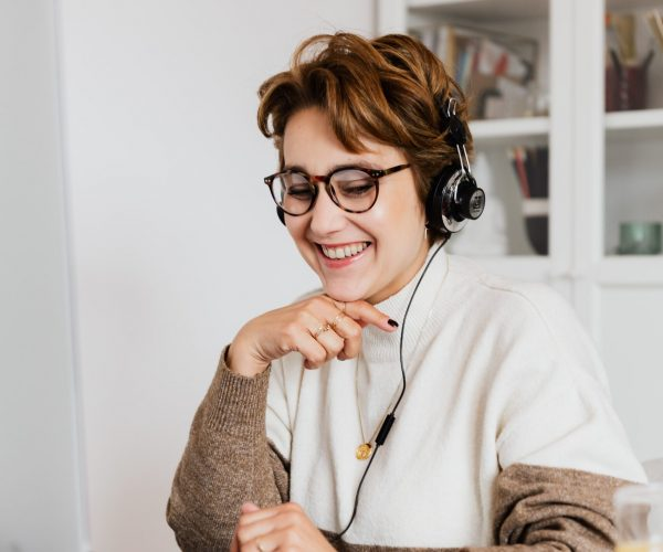 woman laughing while talking on a video call